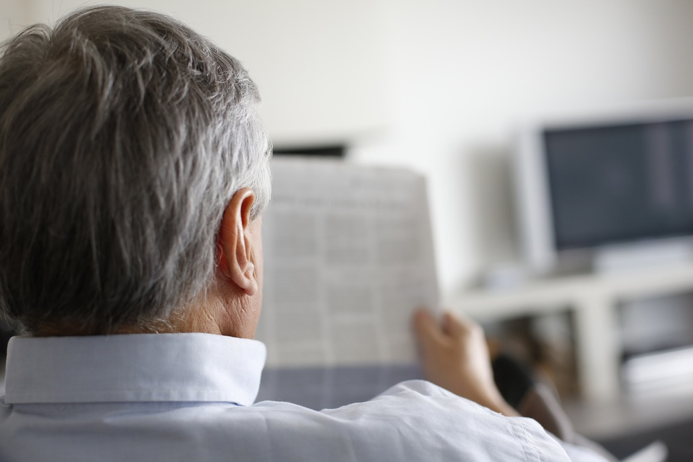 Back view of man reading newspaper at home.jpeg